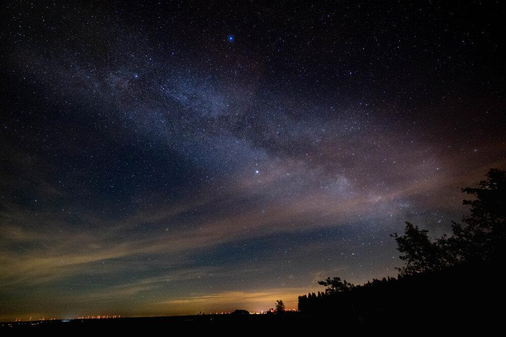 Een prachtige, open sterrenhemel vlak bij het hoogste punt van België: Signaal van Botrange (694 meter). In de verte zie je de lichtgloed van de stad.