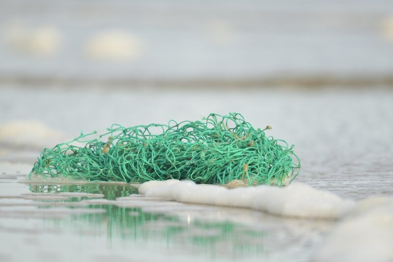 Een aangespoeld visnet aan de kust.