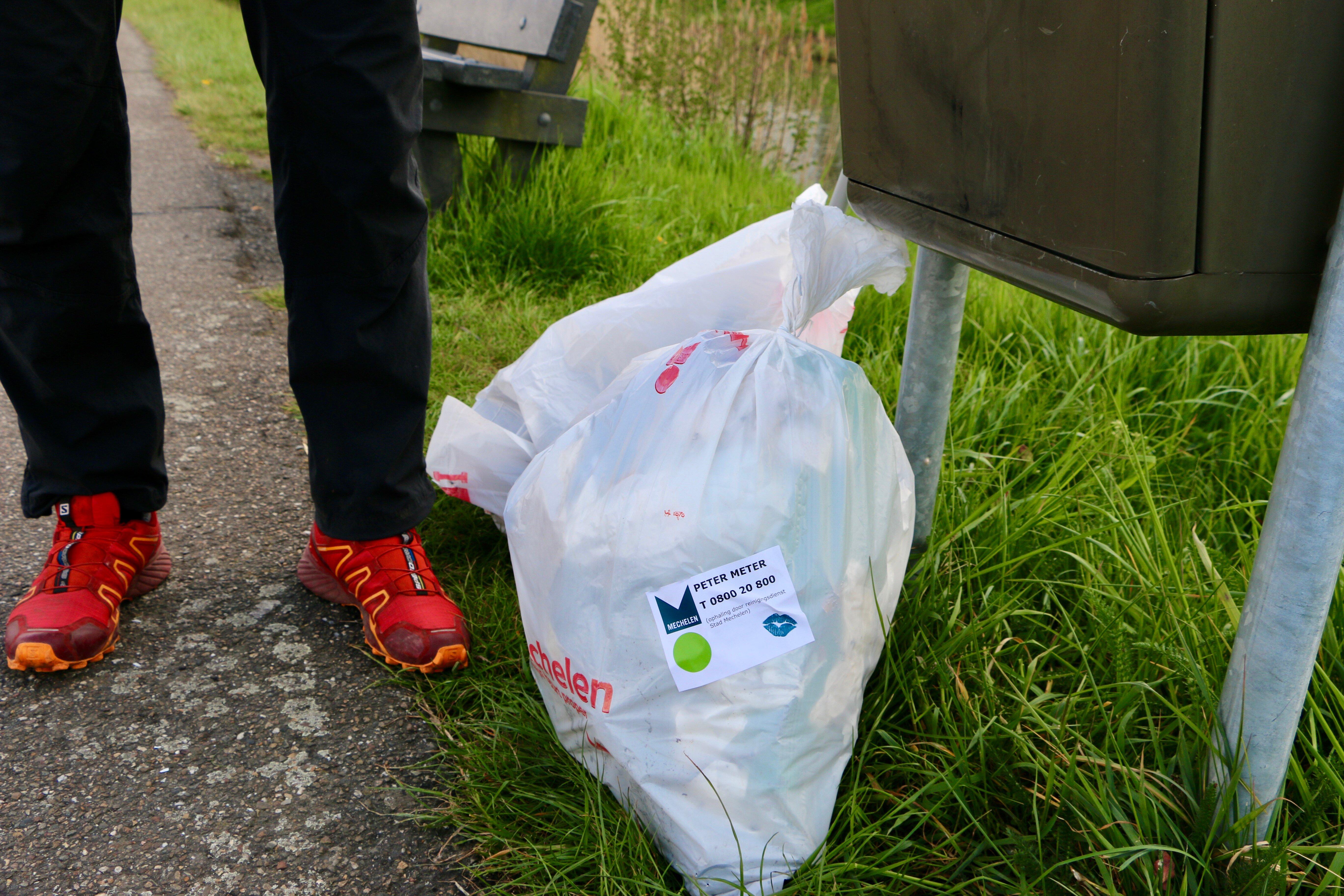 Een vuilniszak van de gemeente gevuld met afval dat onderwerp werd opgeraapt.